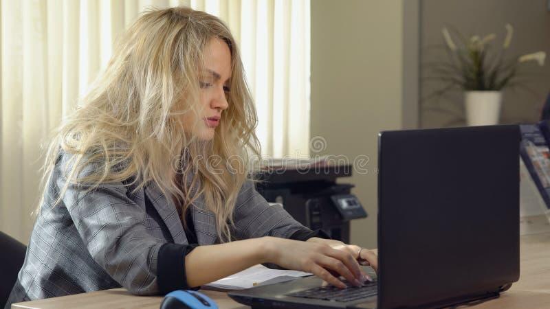Zmęczona biznesowa kobieta w kostiumu pracuje przy komputerem w biurze obrazy stock