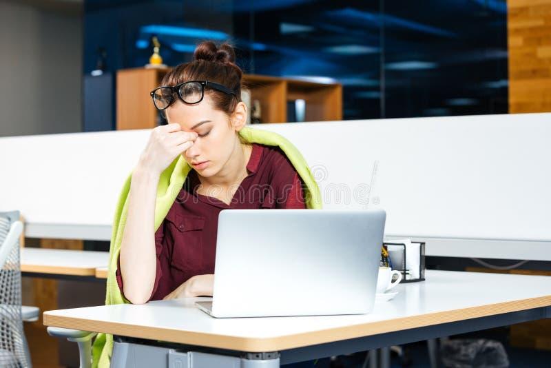 Zmęczona biznesowa kobieta w szkła działaniu z laptopem na miejscu pracy zdjęcie stock