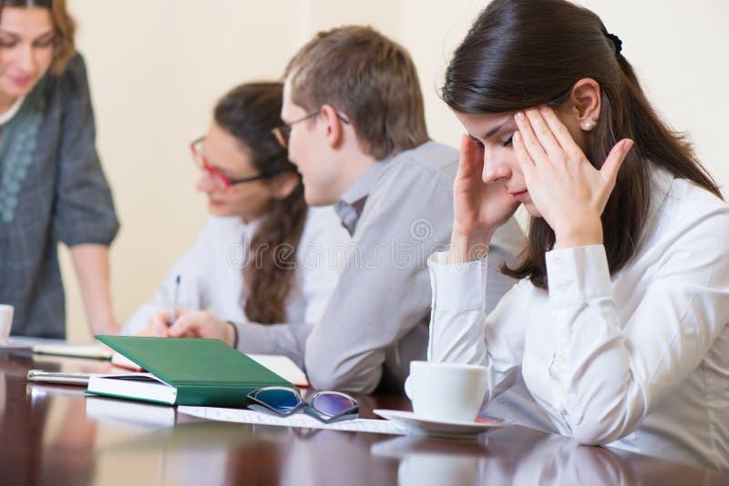 Zmęczona biznesowa kobieta z migreną przy konwersatorium zdjęcia stock