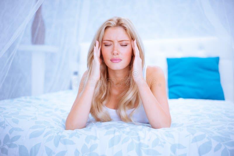 Zmęczona blondynki kobieta w jej sypialni zdjęcia royalty free