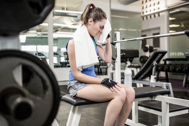 Zmęczona brunetka na ławki obcierania pocie z ręcznikiem zdjęcie royalty free