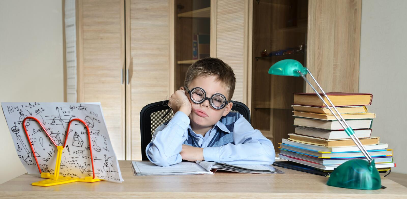 Zmęczona chłopiec Jest ubranym Śmiesznych szkła Robi pracie domowej dziecka szykan target187_1_ Chłopiec Ma problemy Z Jego pracą obraz royalty free