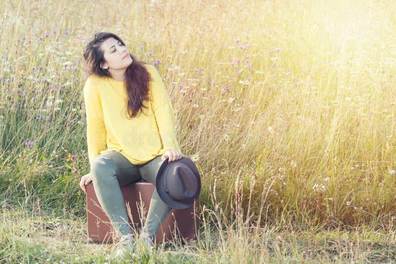 Zmęczona dziewczyna z kapeluszowym obsiadaniem i odpoczywać na brown rocznik walizce w śródpolnej drodze podczas lato zmierzchu S fotografia stock