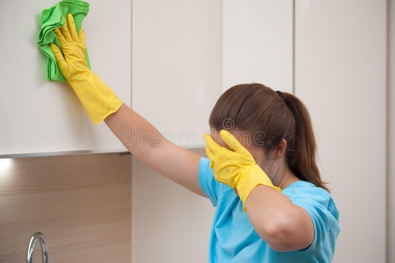 Zmęczona gospodyni domowa w gumowych rękawiczkach po czyścić obrazy stock