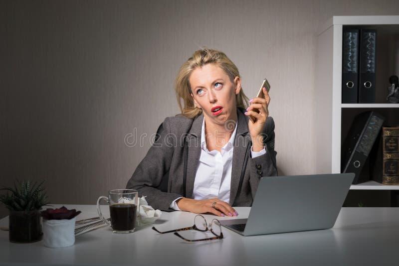 Zmęczona kobieta ma nudną rozmowę telefoniczną przy pracą obrazy royalty free