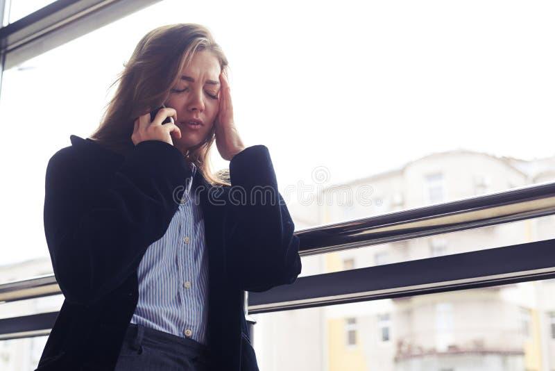 Zmęczona kobieta opowiada na telefonie z ręką na czole zdjęcie royalty free