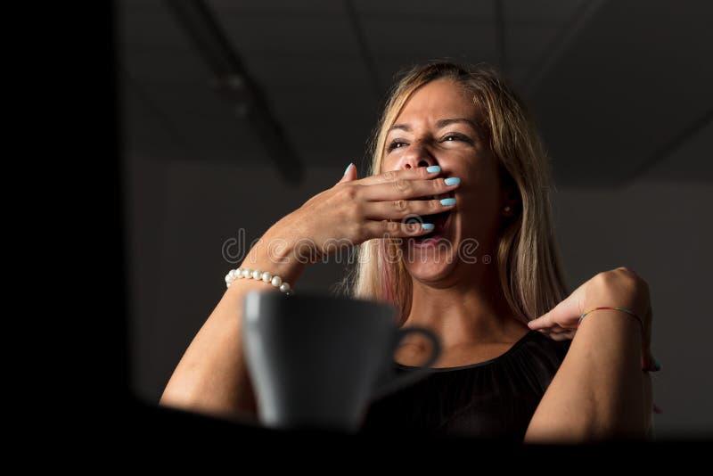 Zmęczona kobieta pracuje póżno przy nocą zdjęcie stock