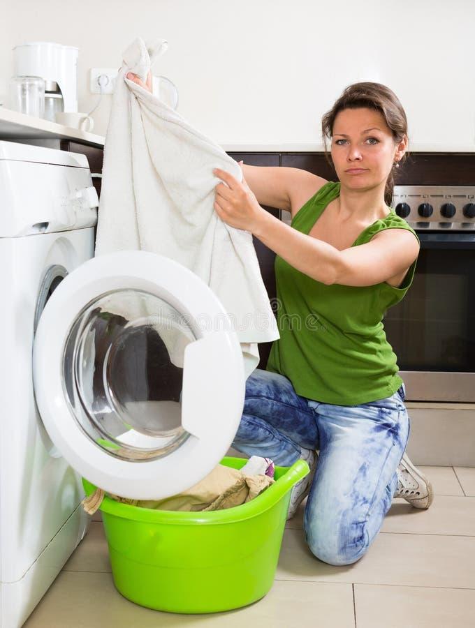 Zmęczona kobieta robi pralni w domu obraz royalty free