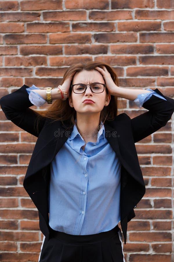 Zmęczona młoda kobieta w kostiumu utrzymuje jej głowę zdjęcia stock