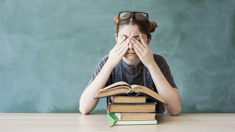 Zmęczona młoda studencka dziewczyna z książkami obraz stock