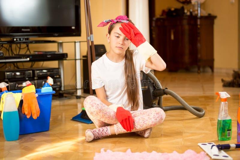 Zmęczona nastolatek dziewczyna czyści drewnianej podłoga przy żywym pokojem fotografia stock
