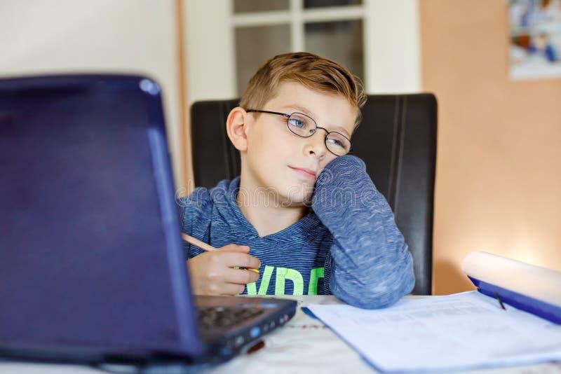Zmęczona smutna dzieciak chłopiec z szkłami robi szkolnej pracie domowej z notatnikiem w domu Przygnębiony dziecko pisze eseju z  obrazy royalty free