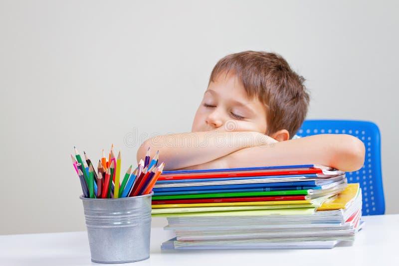 Zmęczona szkolna chłopiec śpi obsiadanie przy stołem z dużym stosem książki, podręczniki i notatniki, obrazy stock