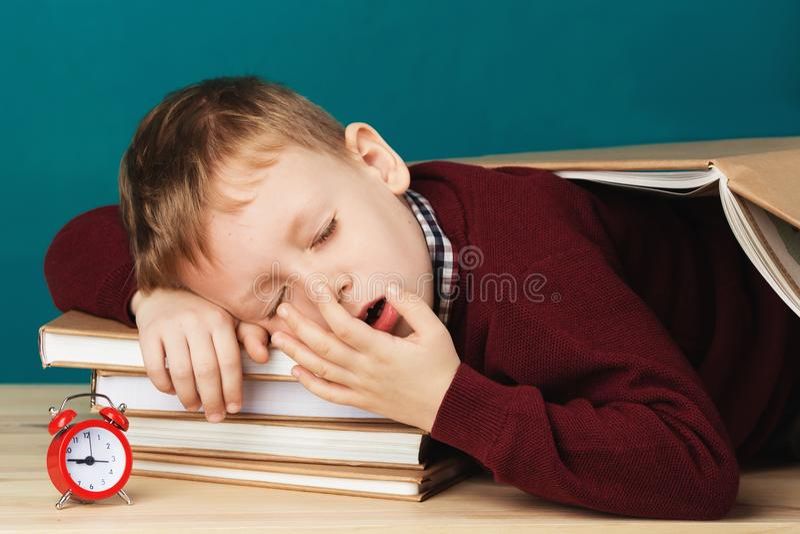 Zmęczona szkolna chłopiec uśpiona na książkach mały studencki dosypianie na tex zdjęcia stock