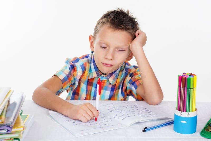 Zmęczona szkolna chłopiec z smutną twarzą robi lekcjom obraz stock