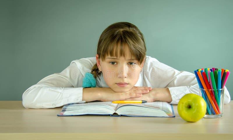 Zmęczona uczennica odpoczywa na książce na biurku zdjęcia royalty free