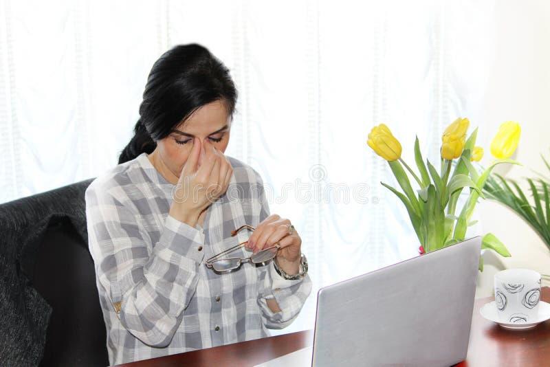 Zmęczona wykonawcza kobieta przed jej laptopem przy pracą, obraz royalty free
