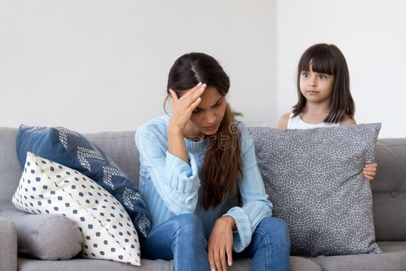 Zmęczona zaakcentowana macierzysta czuciowa migrena odmawia bawić się z dzieciakiem obraz stock