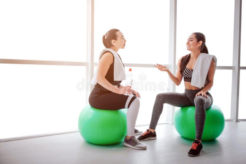 Zmęczone ale szczęśliwe młode kobiety siedzą przy fitballs i opowiadają One uśmiechają się each inny Modele białych ręczniki na i obrazy stock