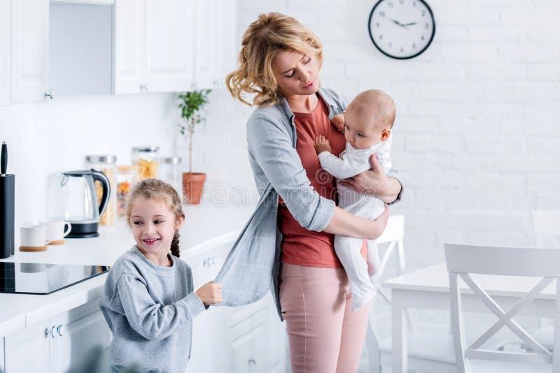 zmęczonego macierzystego mienia dziecięcy dziecko podczas gdy niegrzeczna córka trzyma jej kardigan royalty ilustracja