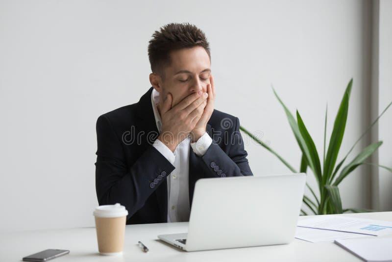Zmęczonego urzędnika ziewające pracujące długie godziny obrazy stock