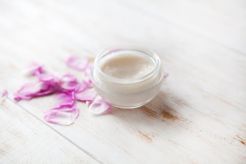 Zmęczonej skóry skincare leczenia kosmetyczna kremowa twarzowa terapia twarzy śmietanka z różanymi płatkami na białym tle fotografia stock
