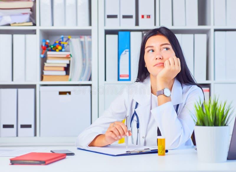 Zmęczony żeński lekarz medycyny w białym medycznym opatrunkowej togi czekaniu dla pacjentów przy biurem zdjęcie royalty free