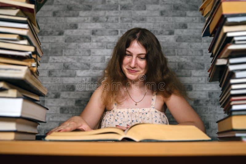 Zmęczony żeńskiego ucznia czytanie wśród książek Zadumany młodej kobiety obsiadanie przy stołem z stosem książka dalej i czytanie fotografia royalty free