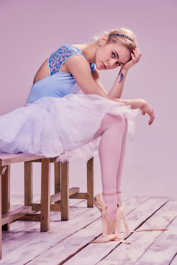 Zmęczony baletniczego tancerza obsiadanie na drewnianej podłoga zdjęcie royalty free