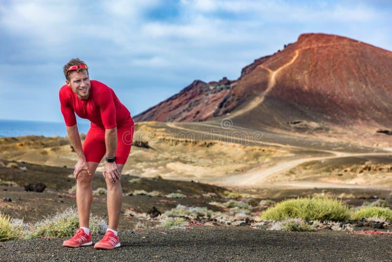 Zmęczony biegacz na śladzie biega uczucie wyczerpującego i odwodnionego od upału Atleta mężczyzna z smartwatch bierze przerwę łap zdjęcia stock