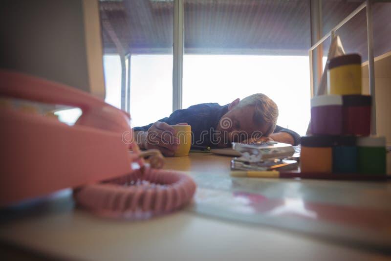 Zmęczony biznesmena drzemanie na biurowym biurku fotografia stock