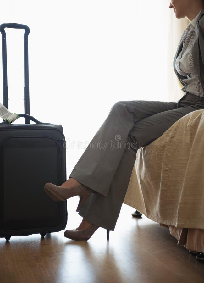 Zmęczony biznesowej kobiety obsiadanie na łóżku w pokój hotelowy obrazy royalty free