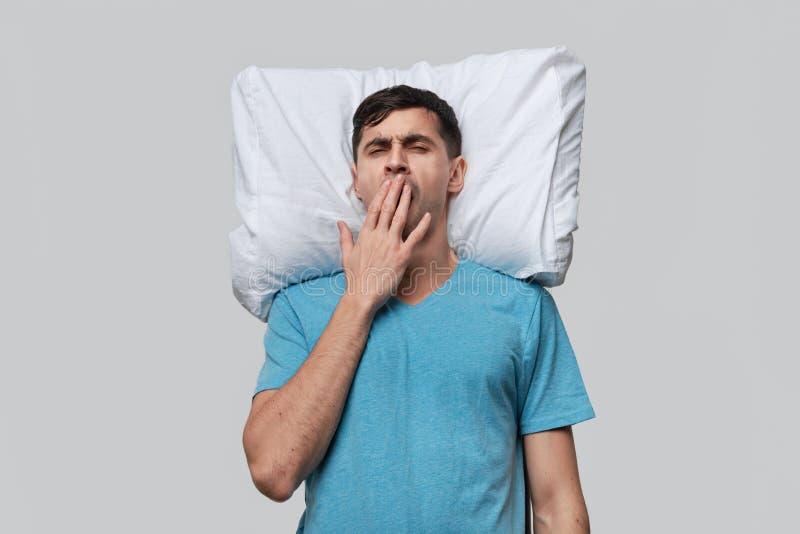 Zmęczony brunet w niebieskim koszulku, spoczywający na białej poduszce wyizolowanej na szarym tle obraz royalty free