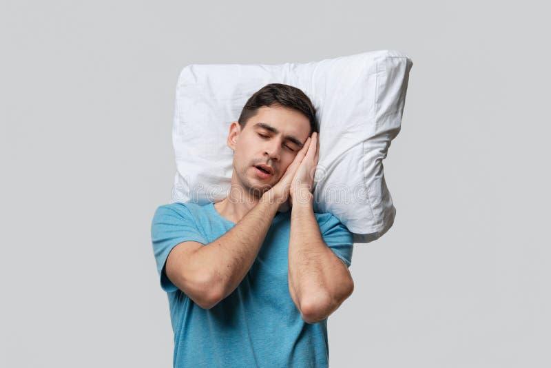 Zmęczony brunet w niebieskim koszulku, spoczywający na białej poduszce wyizolowanej na szarym tle zdjęcia royalty free