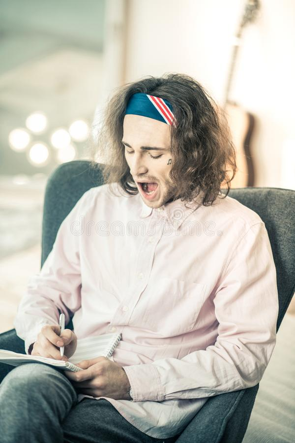 Zmęczony długowłosy utalentowany mężczyzna z tatuażem na twarzy ziewaniu obraz stock