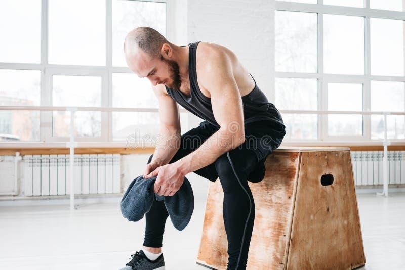 Zmęczony dysponowany mężczyzna odpoczywa po ciężkiego przecinającego szkolenia w sprawności fizycznej gym i chwyta ręczniku w ręk obrazy stock