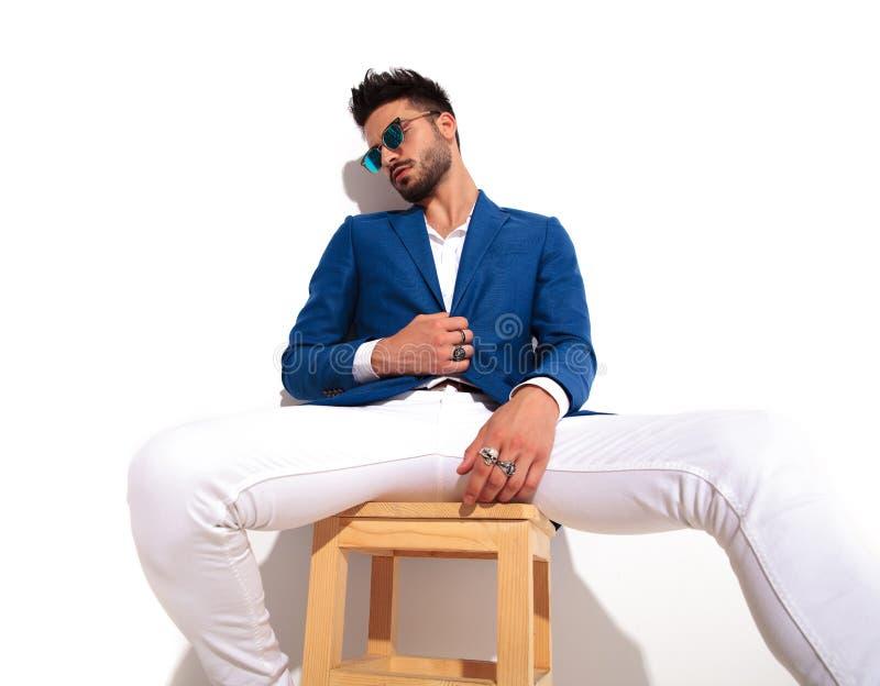 Zmęczony elegancki mężczyzna jest ubranym okulary przeciwsłonecznych siedzi na krześle zdjęcie stock