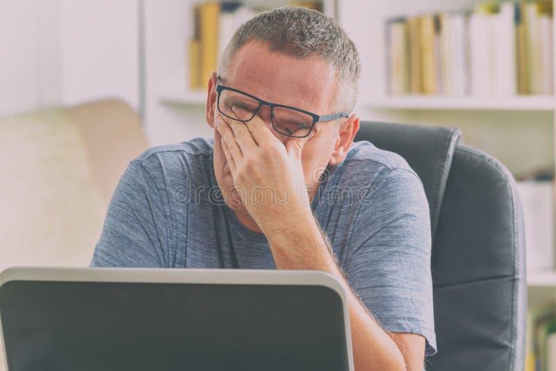 Zmęczony freelancer mężczyzna naciera jego ono przygląda się obraz stock