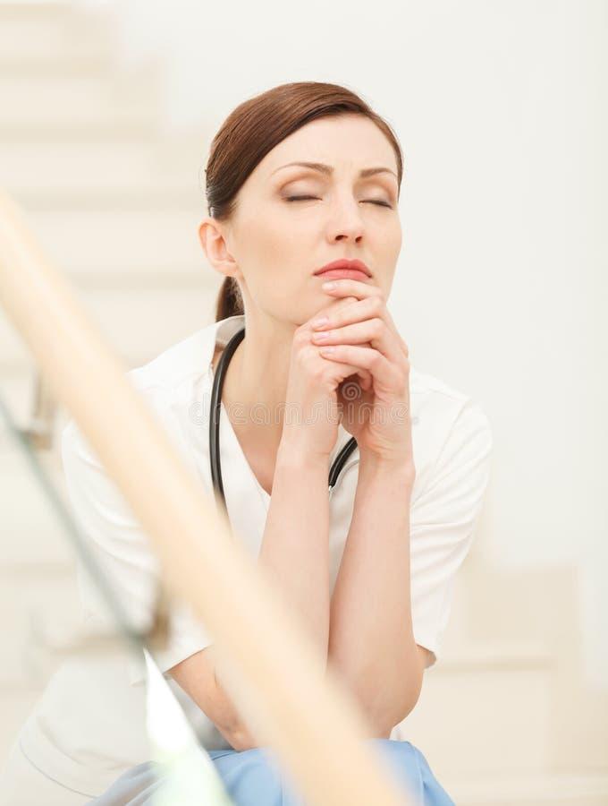 Zmęczony i przygnębiony. Piękny młody kobiety lekarki obsiadanie przy th obrazy royalty free