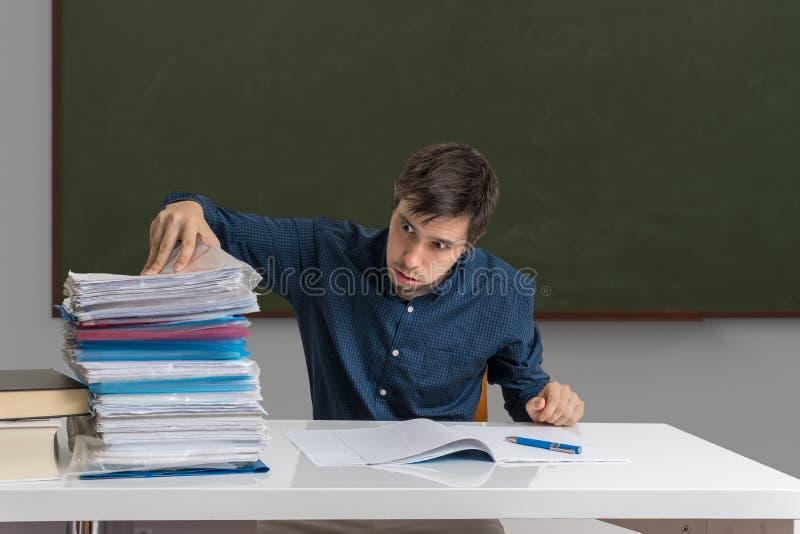 Zmęczony i skołowany nauczyciel koryguje wiele egzaminy w sala lekcyjnej fotografia royalty free