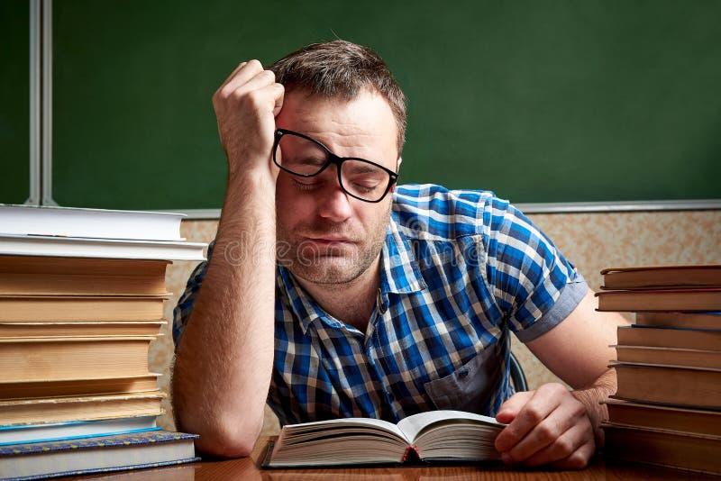 Zmęczony i torturujący rozkudłany uczeń w szkłach śpi przy stołem z stertami książki obrazy stock