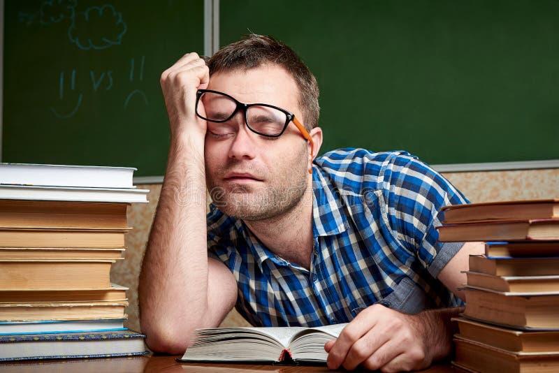 Zmęczony i torturujący rozkudłany uczeń w szkłach śpi przy stołem z stertami książki obraz stock