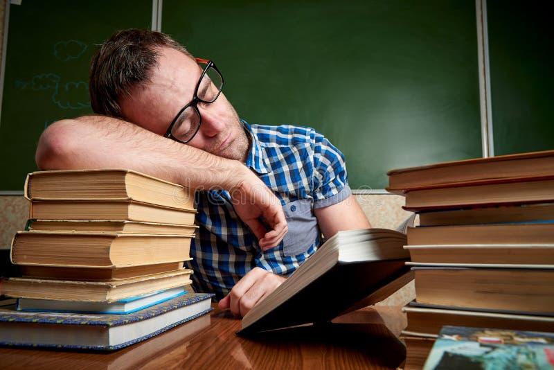Zmęczony i torturujący rozkudłany uczeń w szkłach śpi przy stołem z stertami książki zdjęcia stock
