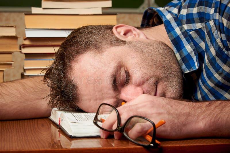 Zmęczony i torturujący rozkudłany uczeń z szkłami śpi przy stołem z stertami książki obraz royalty free