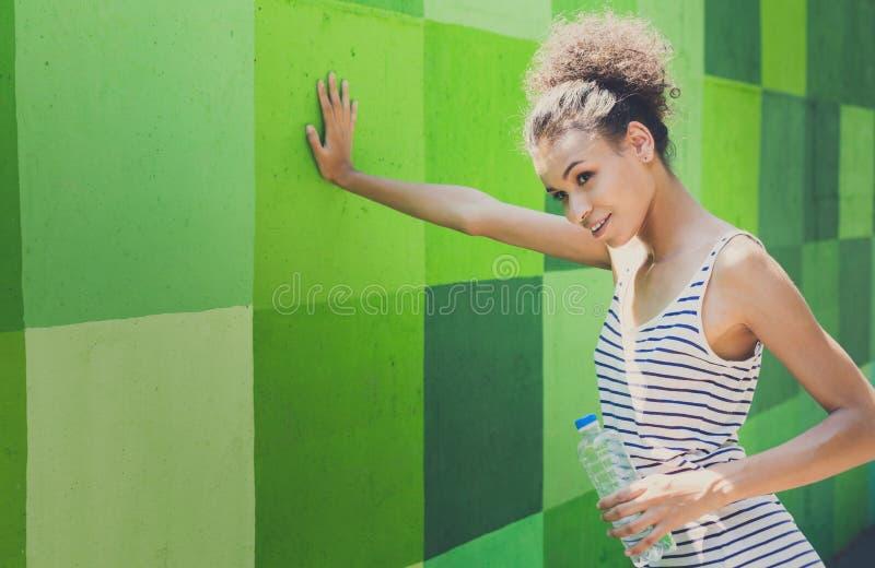 Zmęczony kobieta biegacz ma przerwę, opiera na zieleni ścianie obrazy royalty free