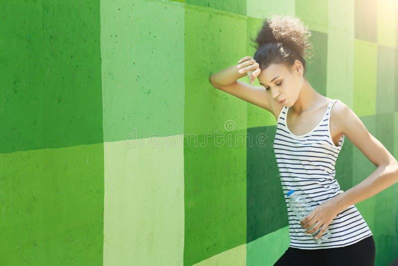 Zmęczony kobieta biegacz ma przerwę, opiera na zieleni ścianie obraz royalty free
