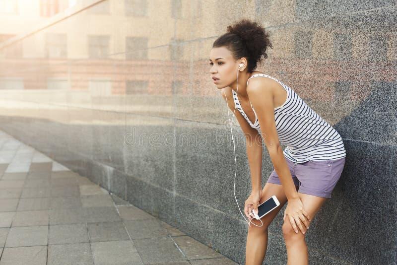 Zmęczony kobieta biegacz ma przerwę, stoi blisko popielatej ściany fotografia royalty free