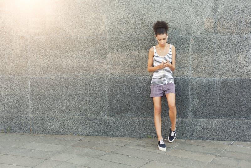 Zmęczony kobieta biegacz ma przerwę, stoi blisko popielatej ściany obrazy royalty free