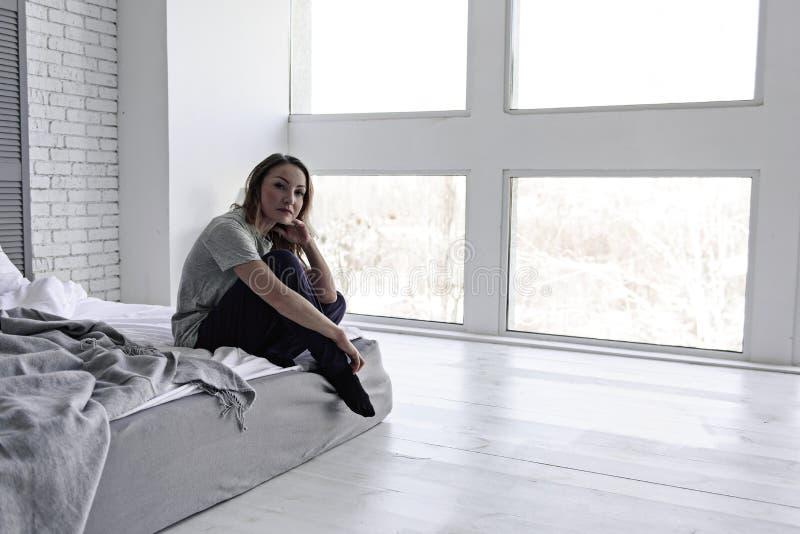 Zmęczony kobiety obsiadanie na łóżku zdjęcie royalty free