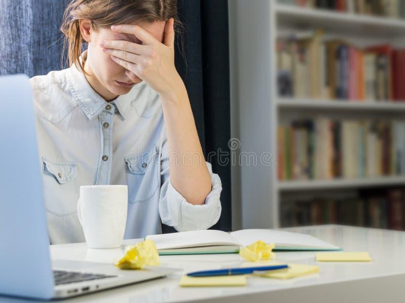 Zmęczony lub skołowany osoby obsiadanie przy biurkiem obrazy royalty free